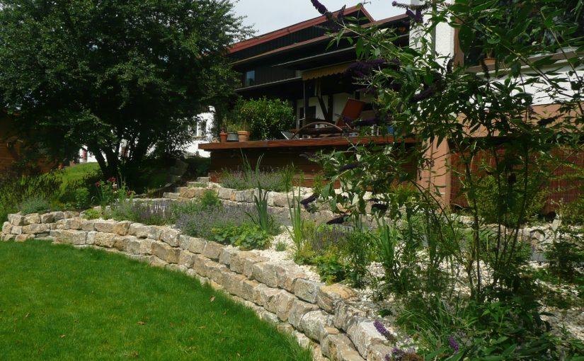 Hanggrundstück Garten Umgestaltung. Terrassiert, mit Gartenmauer und Staudenbeeten.