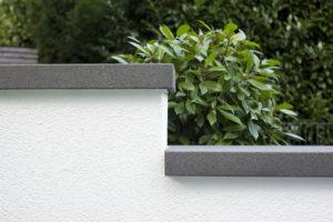 Grundstücksmauer mit Abdeckung aus grauen Steinplatten